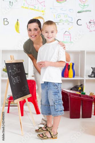 happy young teacher and preschool boy in classroom
