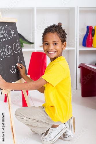 cute indian preschool boy writing on chalkboard