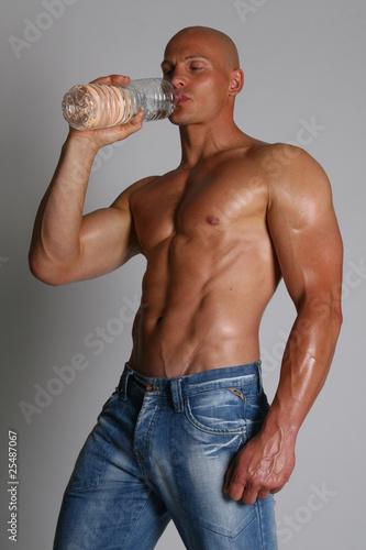 Leinwandbild Motiv muskulöser Mann mit Flasche