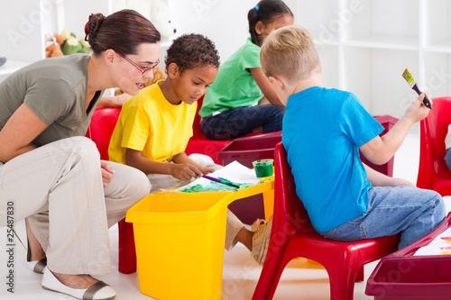 preschool teacher helping kids paint pictures