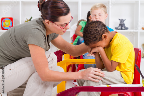 teacher comforting crying preschool boy