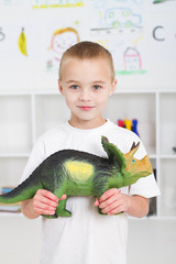 preschool boy playing with dinosaur