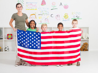 american teacher and preschool students holding flag