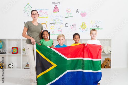 south african teacher and preschool kids holding flag