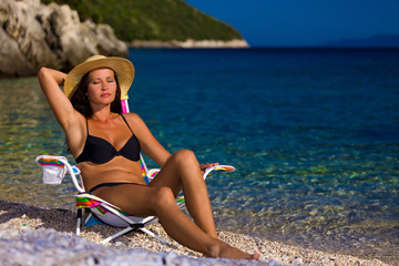 Woman in black bikini and straw hat tans on deckchair in beauty