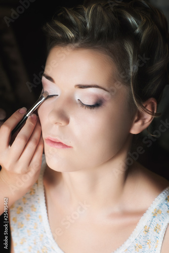 applying eye shadow with selective focus