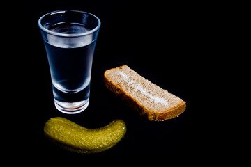 Vodka shot with snacks isolated on black