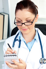 Serious female doctor smiling at the camera holding a notepad in