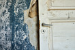 Torn wallpaper and wooden door in abandoned house.