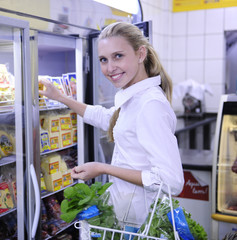 Woman shopping for frozen food in the supermarket