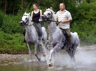 Ein Mann und eine Frau reiten durch eine Fluss
