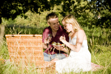 A young couple sitting on the grass, having a picnic