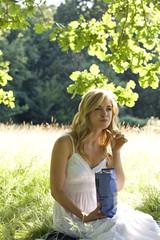 A young woman sitting on the grass, eating crisps