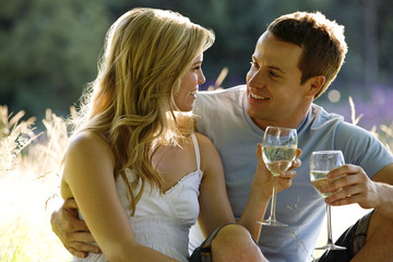 A young couple sitting on the grass, drinking wine