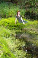 The girl sits on the bank of wood lake