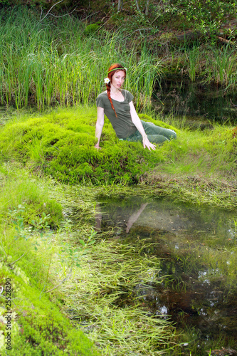 The girl sits on the bank of wood lake