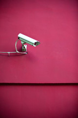 Security camera attached on red building