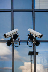 Two security cameras attached on business building with reflecti