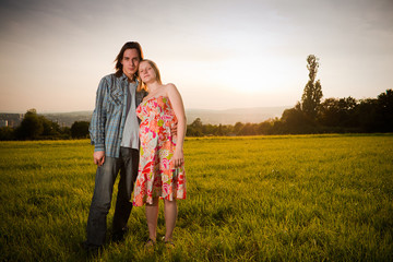 Young lovely couple flirt in mountain field on sunset