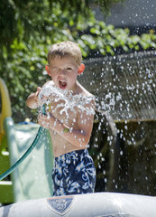 Young Boy playing in the garden with a hosepipe