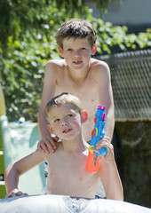 Two young brothers posing in the garden on a summers day