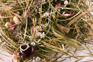 Beads with roses petals on hay