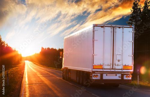 Leinwandbild Motiv White truck on the asphalt road in the evening