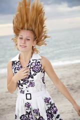 Portrait of beautiful blonde girl with tousle hair on the beach.