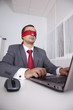 Blindfold businessman working with his laptop