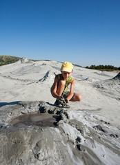 Cute kid playing at the muddy volcanoes