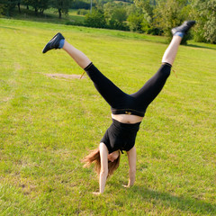 Young girl make handstand
