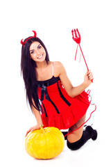 sexy brunette girl sits, dressed in Halloween costume imp, next