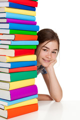 Student sitting behind pile of books on white