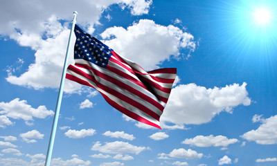 United States Flag in front of vivid, sunny, cloudy sky