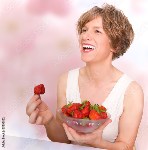 Smiling woman in good mood eating strawberries