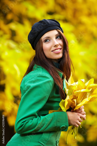 Fashion woman in autumn park holding yellow leaf