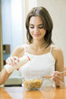 Young happy woman with cereal muslin and milk at home