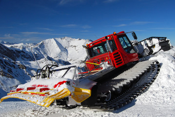 Red snowplow on a slope
