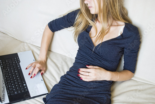 Young bored girl lying on the couch with a notebook