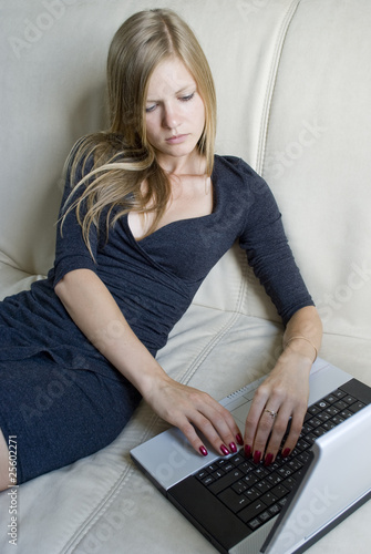 Girl sitting on the couch and chatting in her notebook