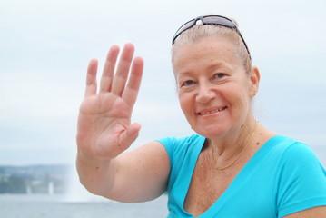 Eine Frau am See winkt in die Kamera.