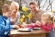 Family Decorating Easter Eggs On Table Outdoors