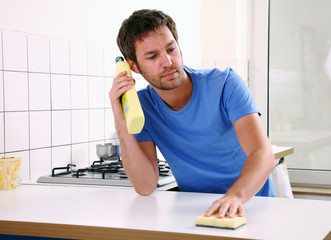 junger mann putzt küche