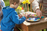 Father And Son Decorating Easter Eggs On Table Outdoors