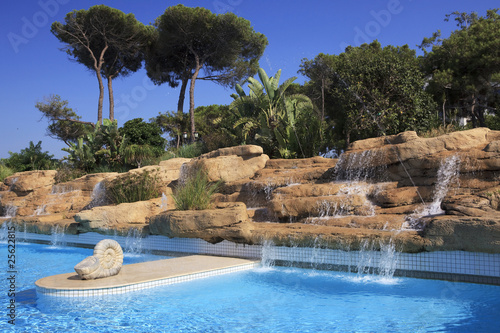 Artificial waterfall in the pool. - 25622815