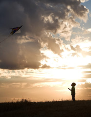 A young boy aims for the sky with his kite.