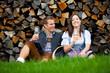 Leinwanddruck Bild - Paar in Tracht sitzt vor Holzstapel und trinkt Wein (Steiermark/