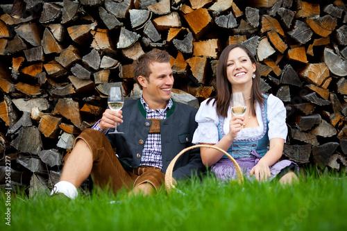 Leinwanddruck Bild Paar in Tracht sitzt vor Holzstapel und trinkt Wein (Steiermark/