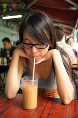 girl drinking a Hong Kong-style milk tea in Dai pai dong