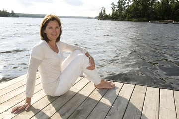 Woman Relaxing On Dock, Lake Of The Woods, Ontario, Canada